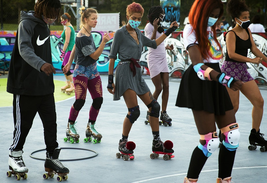 caption: Jaida Morgan, center, practices a move being taught by Tiffany Mason, (not pictured), founder of Roll Around SeaTown, on Monday, September 28, 2020, at the Judkins Park sports courts in Seattle.
