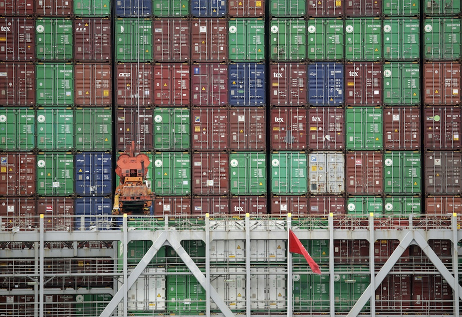caption: Cargo containers are stacked on a ship at California's Port of Los Angeles.