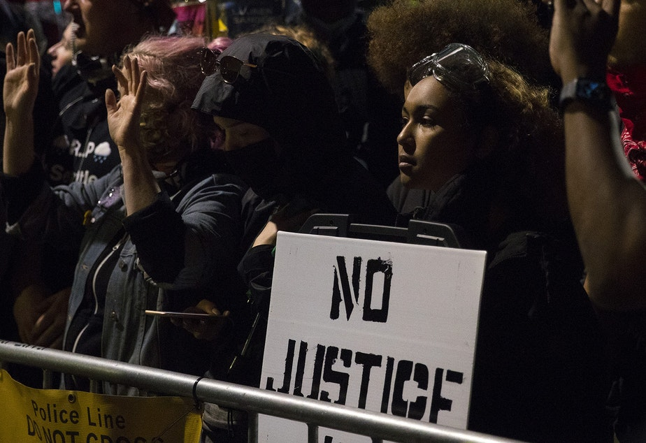 caption: For more than six hours, hundreds of people demonstrating for racial justice and against police brutality stood opposite of a barricade facing Seattle police officers near the department's East Precinct building on Tuesday, June 2, 2020, at the intersection of 11th Avenue and East Pine Street in Seattle. Around 11:30 p.m., officers released tear gas, flash-bang grenades, pepper spray, and rubber bullets on hundreds of people near Cal Anderson Park.