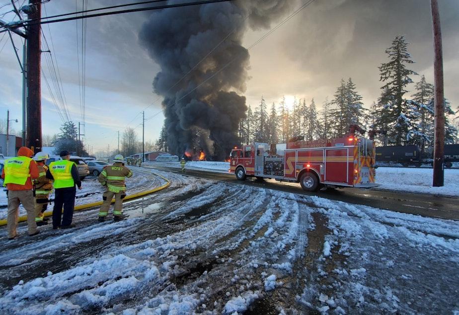 caption: Firefighters watch an oil train burn in Custer, Washington, on Dec. 22, 2020.