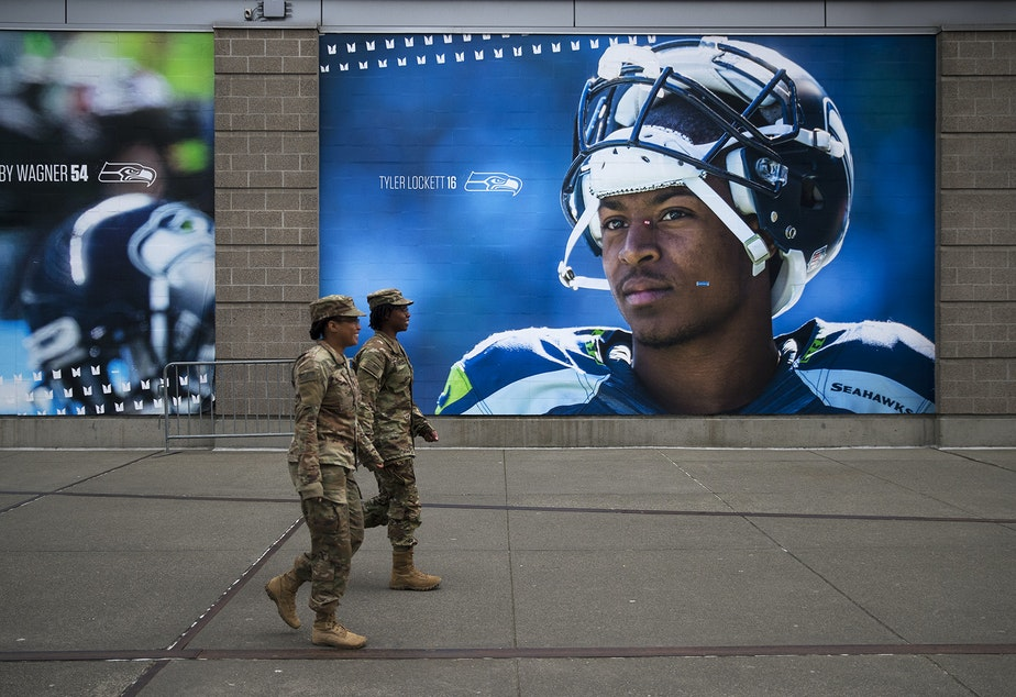 caption: U.S. Army soldiers walk next to a mural of Seahawks wide receiver Tyler Lockett on Tuesday, March 31, 2020, on Occidental Avenue South in Seattle. Soldiers from the 627th Army Hospital from Fort Carson, Colorado, as well as from Joint Base Lewis-McChord set up a 250-bed military field hospital for non COVID-19 patients at the CenturyLink Field Event Center.