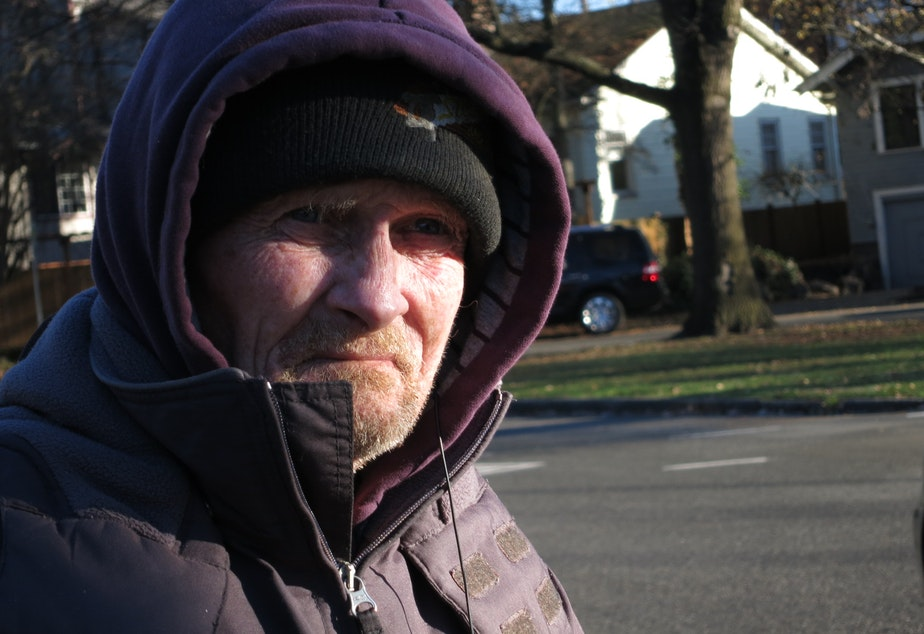 caption: Michael Thompson stands by the NE 65th St. exit from I-5 with a sign asking for help. He suggests providing food, warm clothing, and work to panhandlers.