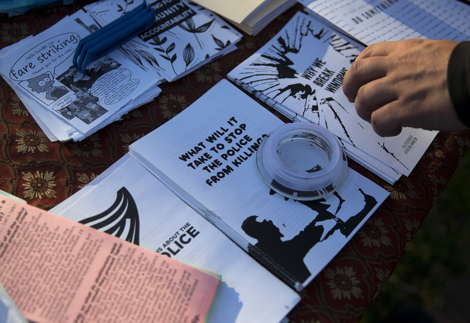 caption: A protester picks up a pamphlet titled, 'Why we break windows,' during a gathering organized by the Seattle Alliance Against Racism and Political Oppression following the reading of the guilty verdict in the trial of Derek Chauvin for the murder of George Floyd, on Tuesday, April 20, 2021, in Seattle.