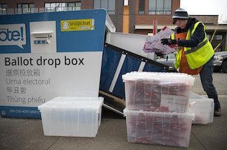 King County Elections employee Josephine Ruff unloads a full ballot drop box outside of the Seattle Public Library in Ballard in November of 2017.