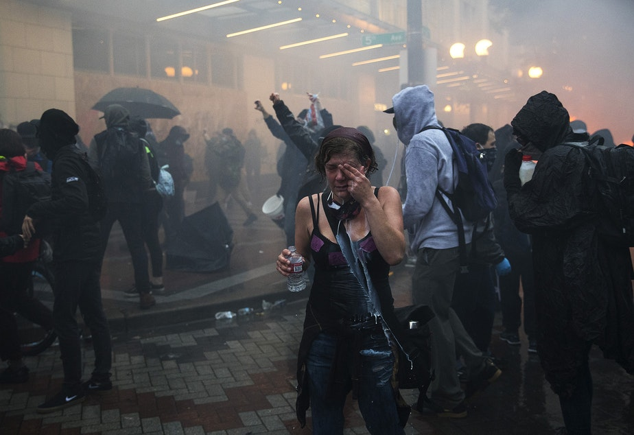 caption: A protester reacts to tear gas near the intersection of 5th and Pine Streets on Saturday, May 30, 2020, in Seattle. Thousands gathered in a protest following the violent  police killing of George Floyd, a Black man who was killed by a white police officer who held his knee on Floyd's neck for 8 minutes and 46 seconds, as he repeatedly said, 'I can't breathe,' in Minneapolis on Memorial Day.
