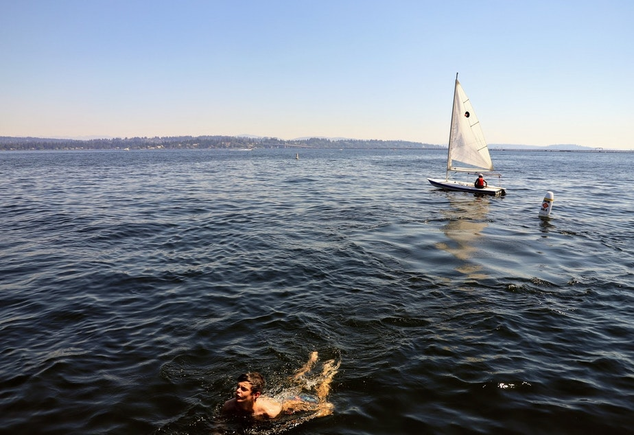 caption: A sailor and a swimmer in Lake Washington near Seattle's Laurelhurst neighborhood on Monday, June 21, 2021, amid record breaking temperatures. The mercury reached 107 at Sea-Tac around the time this photo was taken.