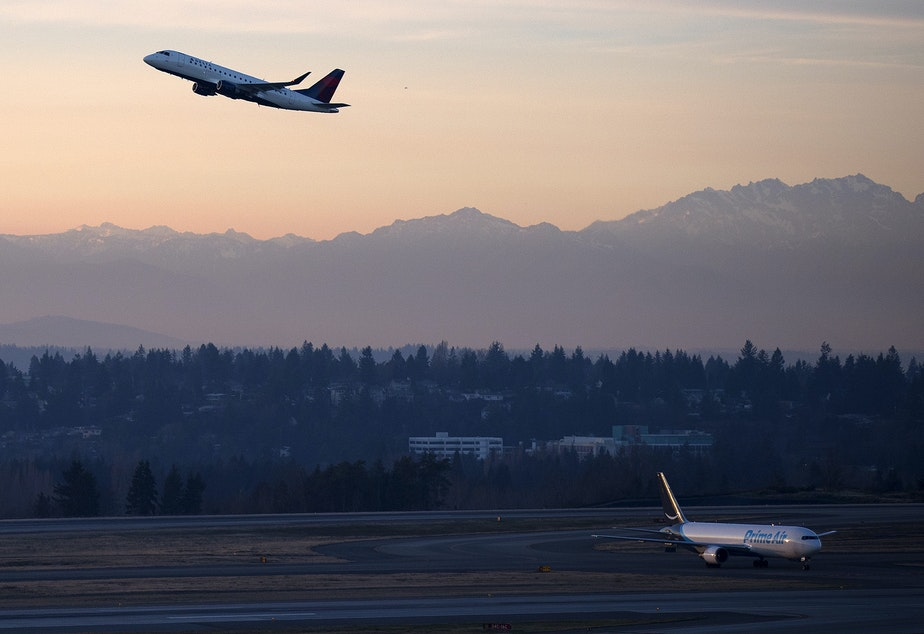 caption: A plane takes off on Monday, December 11, 2017, at Seattle-Tacoma International Airport.