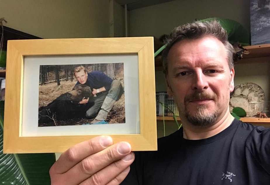 caption: Chris Morgan holds up a picture of himself with Dawson, the grizzly bear he helped catch in the Canadian Rockies while he was in his early twenties.