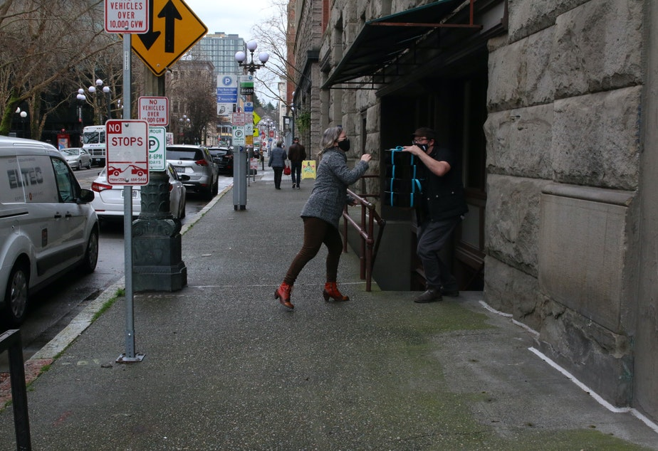 """caption: Erin Brindley and Terry Podgorski of Cafe Nordo hand off boxes to be delivered to customers. They used to do immersive dinner theater. During the pandemic, they've found a way to """"put the experience into a box."""""""