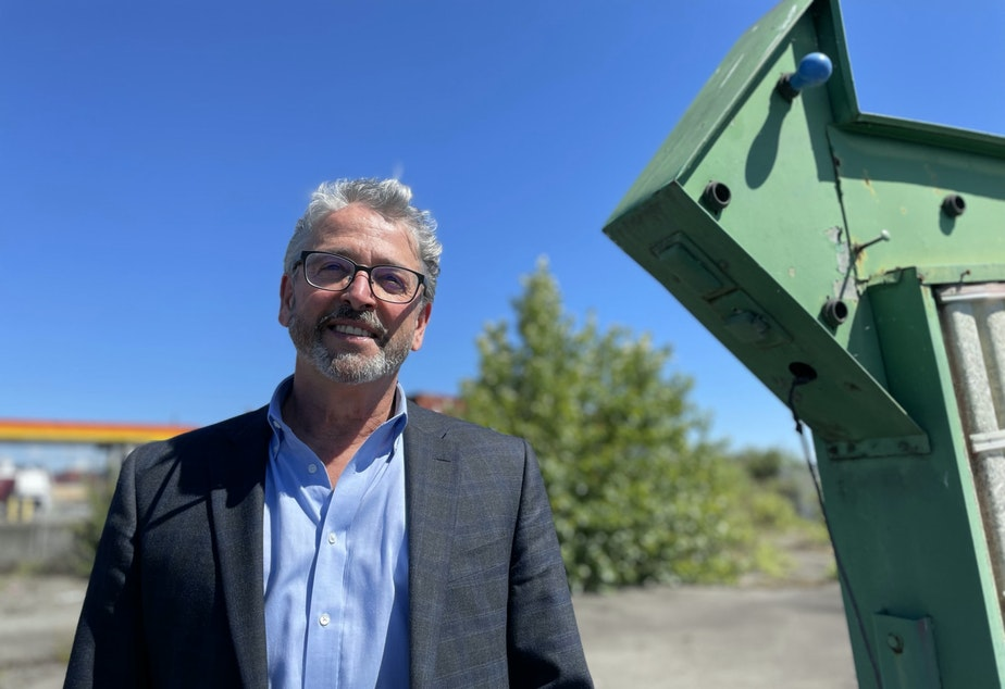 caption: Port Commission President Fred Felleman stands next to an old sign near the east bank of the Duwamish River, across from the Port of Seattle's Terminal 5.