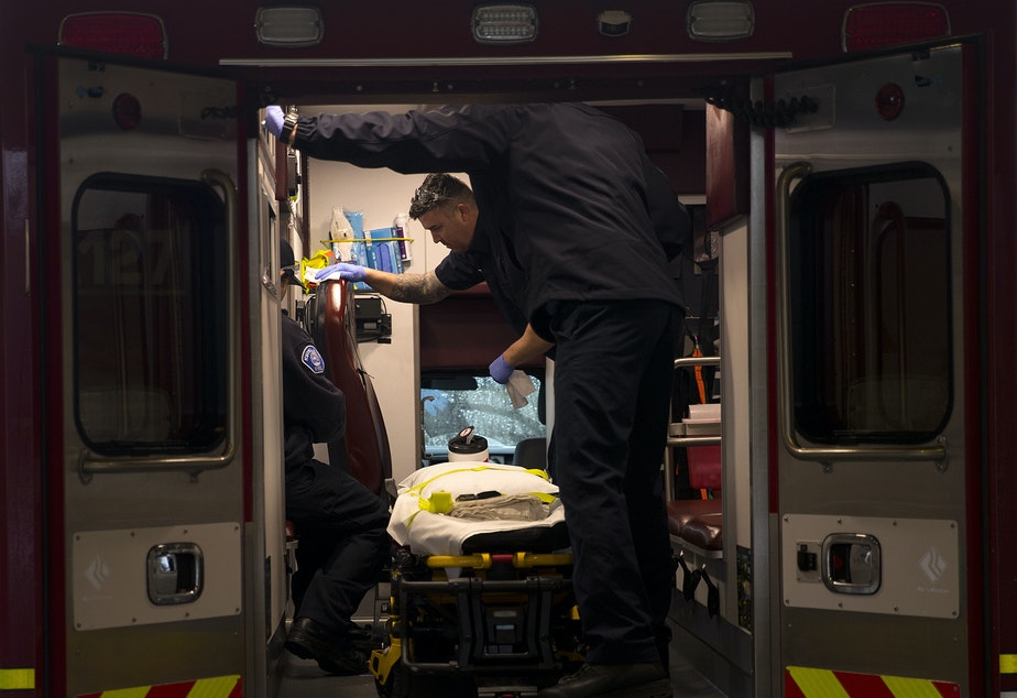 caption: Members of the Kirkland Fire Department disinfect the interior of an ambulance after a patient was transported from the Life Care Center of Kirkland on Monday, March 2, 2020, at Evergreen Health Medical Center in Kirkland.