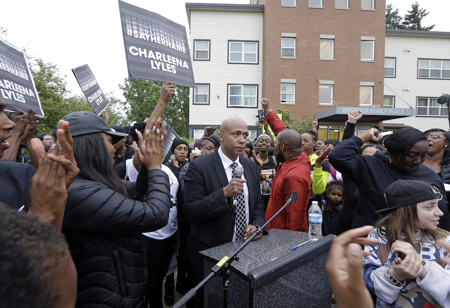 caption: People cheer as attorney James Bible, center, speaks at a memorial outside where a pregnant mother was shot and killed Sunday by police on June 20, 2017 in Seattle.