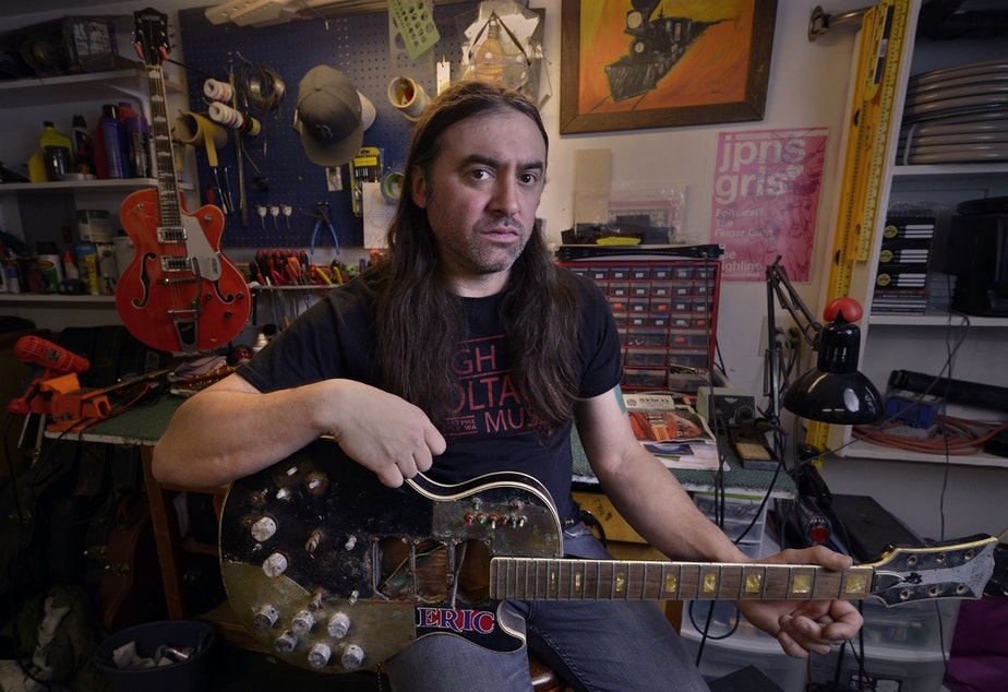 caption: High Voltage Music co-owner Chris Lomba in his backyard shop in north Seattle. He says his shop on Capitol Hill had to close after the loss of a nearby rehearsal space that brought in musicians.