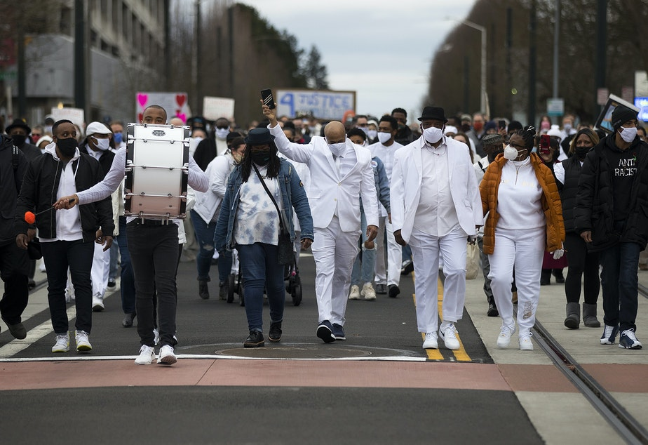 caption: James Bible, the Ellis family's attorney, center, marches silently along with about 200 others to the beat of a single drum, played by drummer Elyshau Wilson, left, in honor of 33-year-old Manuel Ellis who was killed by Tacoma police one year ago, on Sunday, February 28, 2021, along Martin Luther King Jr. Way in Tacoma.
