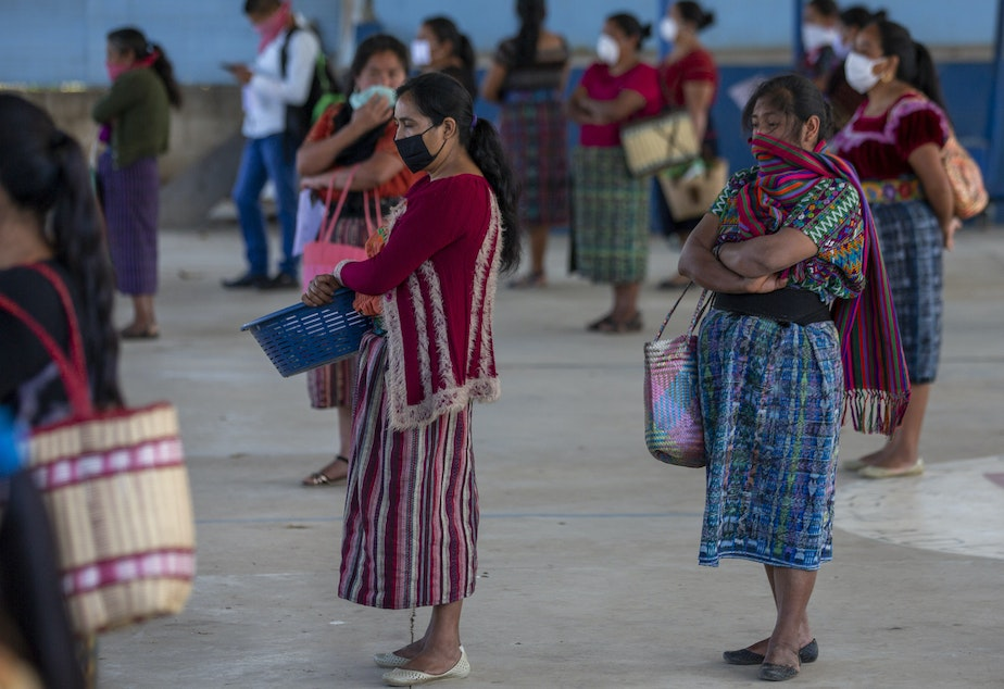 caption: Women wearing face masks stand at a safe distance to help curb the spread of the new coronavirus, as they wait for food assigned to their children outside a school in Xesuj, Guatemala, where many residents depend on remittances, largely from the U.S. The fallout from the pandemic is cutting into the financial lifelines for people across Latin America, Africa and Asia.