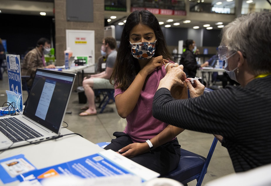 caption: Volunteer Janet Welle administers a Covid-19 vaccine for Shreya Magesh, 23, on Thursday, April 15, 2021, at Lumen Field Event Center in Seattle. As of Thursday, anyone 16 years of age and older is eligible.
