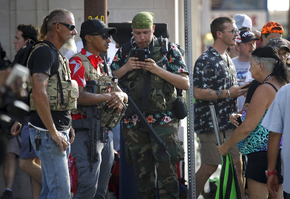 caption: Gun-carrying men wearing the Hawaiian print shirts associated with the Boogaloo movement watch a demonstration near the BOK Center where President Trump held a campaign rally in Tulsa, Okla., Saturday, June 20, 2020.