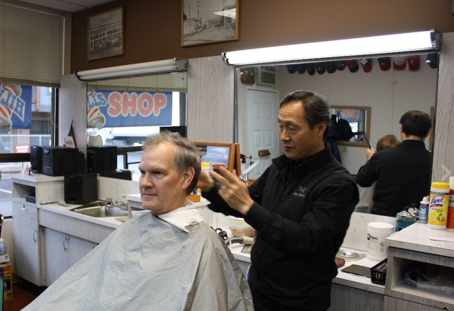 caption: Redmond barber Young Choi discusses the changing face of Redmond with client Kurt Link.