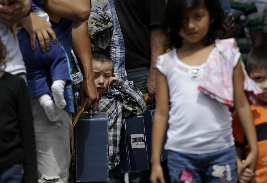 caption: Immigrant families seeking asylum walk to a respite center after they were processed and released by U.S. Customs and Border Protection, Friday, June 29, 2018, in McAllen, Texas.