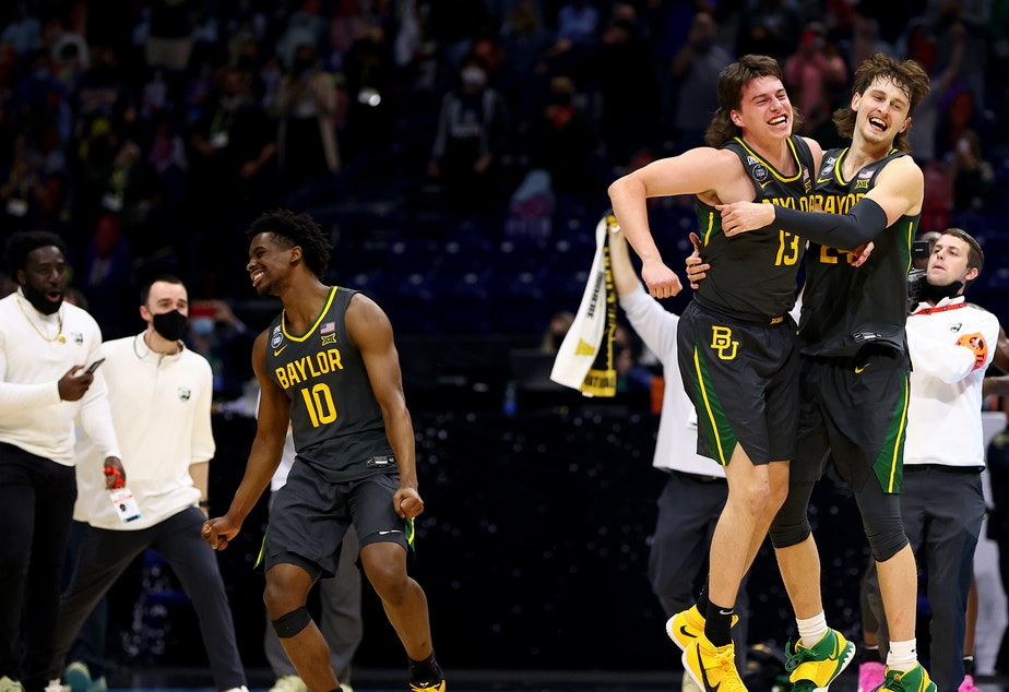 caption: Baylor players Adam Flagler #10, Matthew Mayer #24 and Jackson Moffatt #13 celebrate after defeating the Gonzaga Bulldogs in the National Championship game of the 2021 NCAA Men's Basketball Tournament at Lucas Oil Stadium.