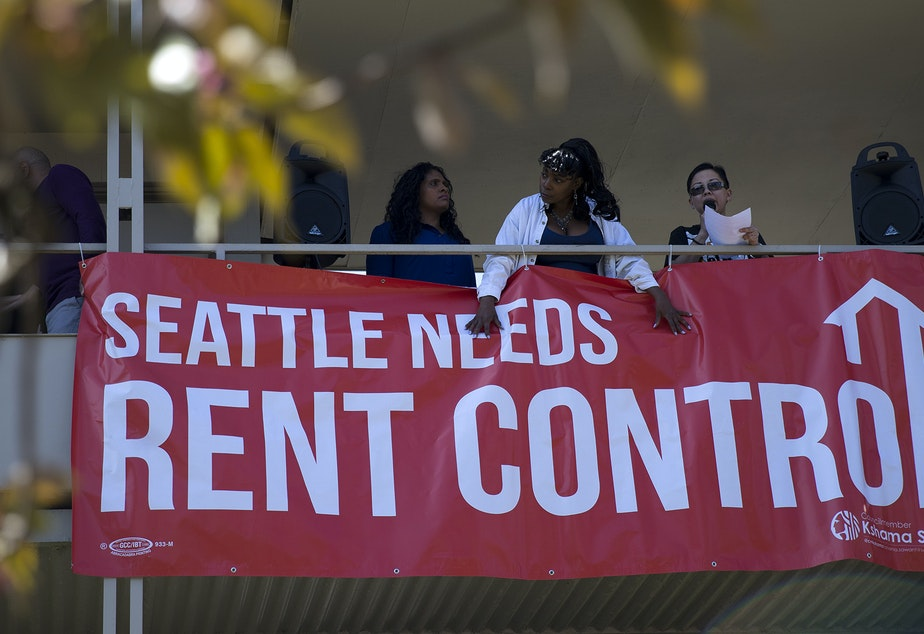 caption: Renee Gordon, center, holds down a Seattle Needs Rent Control sign at the Chateau Apartments on Wednesday, May 1, 2019, during the 20th annual May Day march near the intersection of East Fir Street and 19th Avenue in Seattle.