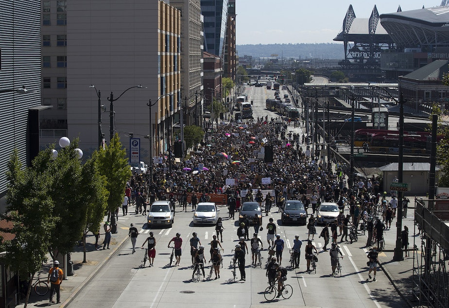 caption: A crowd of around 1,000 people march toward Seattle City Hall during a Defund The Police march from the King County Juvenile Detention Center on Wednesday August 5, 2020, in Seattle.
