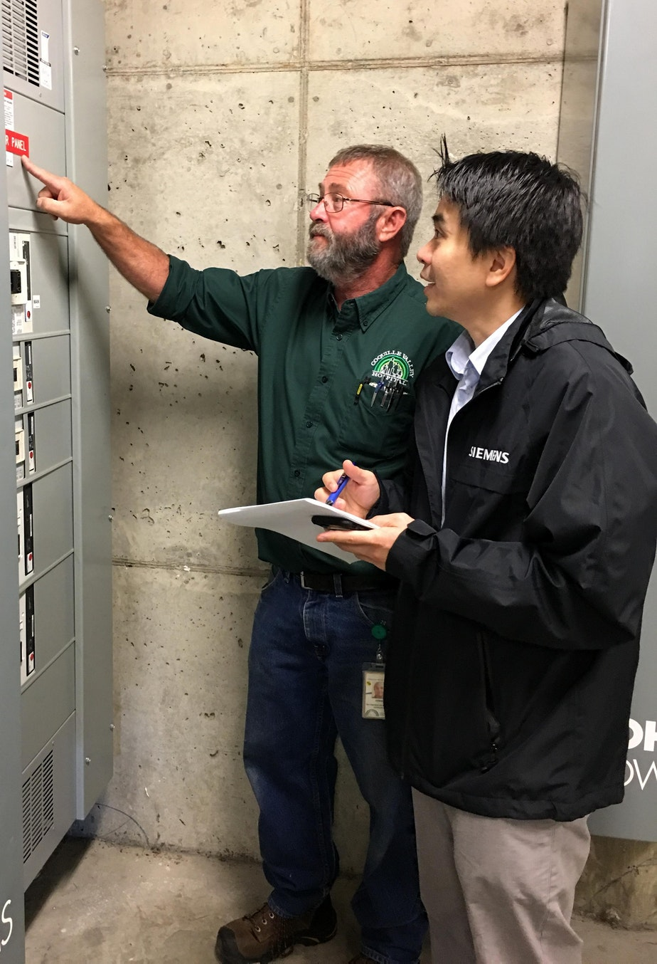 Coquille Valley Hospital plant operations director Ernie Fegles, left, and Andreas Winardi of Siemens discussed how a microgrid might work during a site visit on Sept. 26.