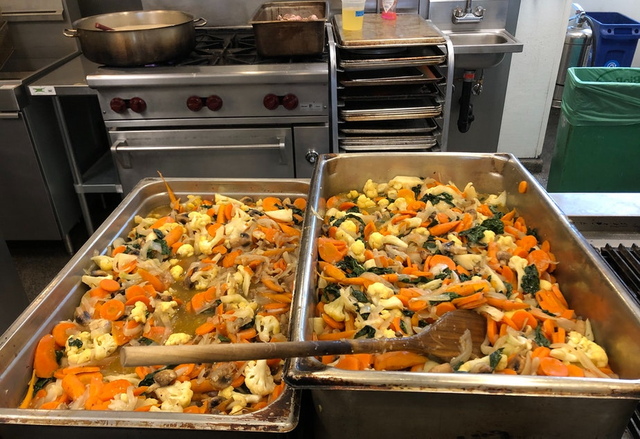 caption: Vegetable stir fry cooling in the kitchen. The food will be portioned and delivered to people in need.