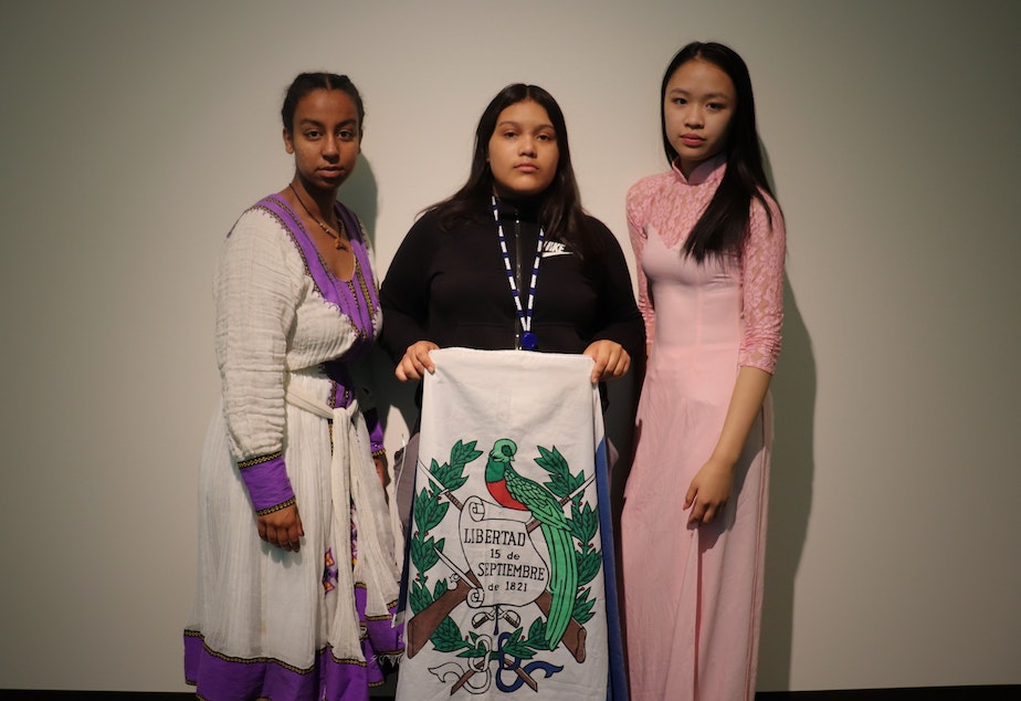 RadioActive's Essey Paulos (left) and Hong Ta (right) wear clothing from their Eritrean and Vietnamese cultures respectively while Michelle Aguilar Ramirez holds the Guatemalan flag.