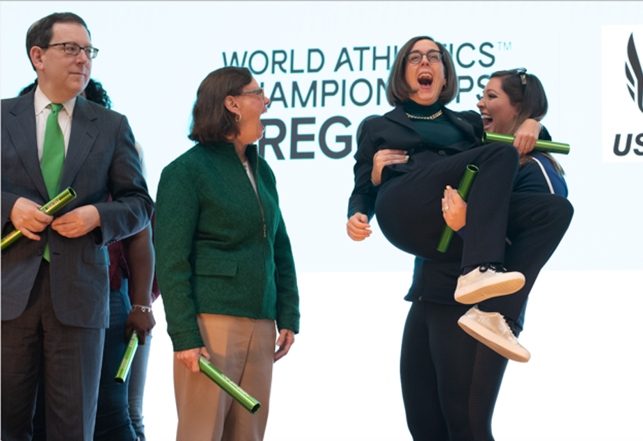 Team USA hammer throw gold medalist DeAnna Price easily lifts Oregon Governor Kate Brown at a kickoff rally Thursday in Eugene for the 2021 World Track and Field Championships.