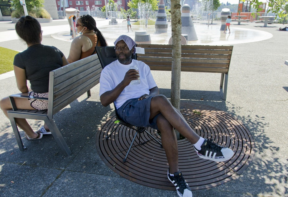 caption: Melvin O'Brien waits in the shade in Yesler Terrace Park while his children play in the spray park during a heat wave hitting the Pacific Northwest, Sunday, June 27, 2021, in Seattle.