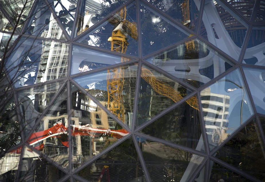 Construction cranes, reflected in the glass at Amazon's Spheres, in Seattle. Amazon's commitment to construction in Seattle is declining as it prepares to transition more growth to HQ2.