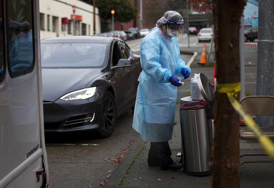caption: Registered nurse Tina Nguyen uses a disinfectant wipe after administering a Covid-19 test on Friday, November 20, 2020, at the International Community Health Services drive thru testing site on 8th Avenue South in Seattle's International District.