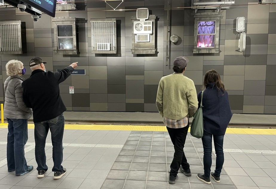 caption: In the U-District station, Annie Han and Daniel Mihalyo of Lead Pencil Studios (right) look at their artwork along with transit riders.
