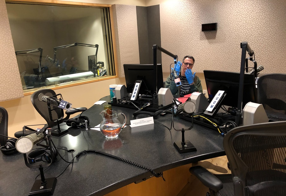 caption: Bill Radke sits alone in studio, with gloves, during the March 20, 2020 Week in Review show.