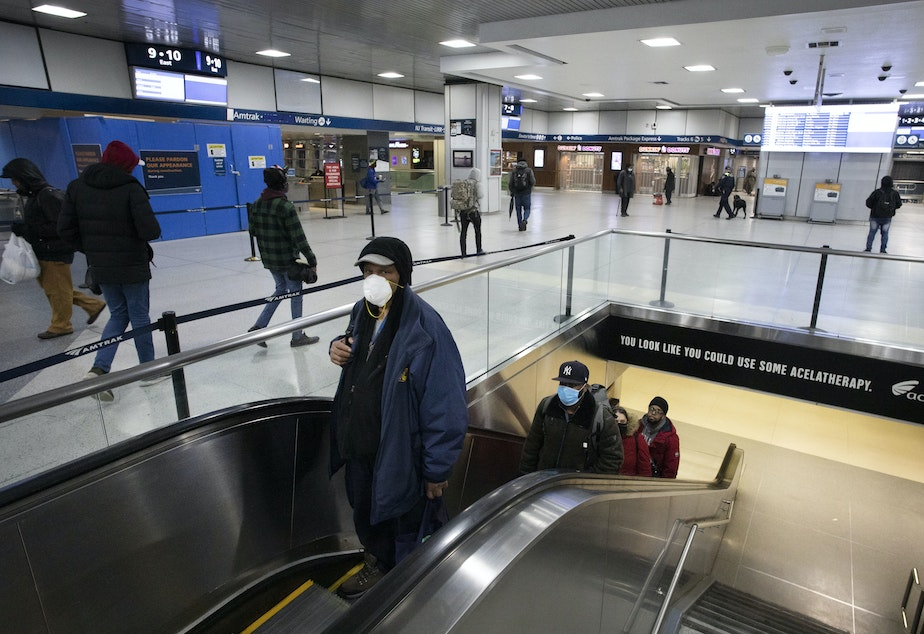 caption: New York Gov. Andrew Cuomo says that in his state — the U.S. epicenter for the coronavirus — the wave of new cases is still going up. Here, commuters wearing masks pass through New York City's Penn Station on Monday.