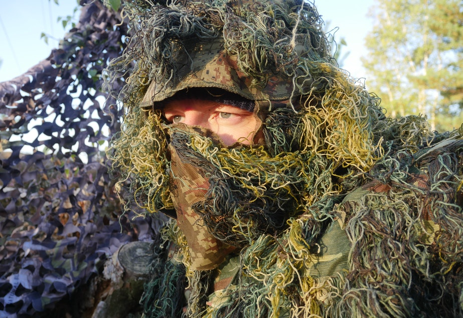 Chris Morgan wearing a ghillie suit as he waits for wolves in Germany.