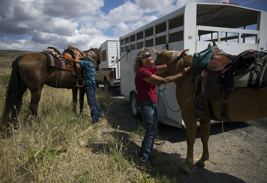 caption: Sue Robbins, left, and Julie Hensley, right, take the saddles off of their horses, Mocha and Hot Rod, after riding near the ranch where Julie grew up, on Tuesday, July 16, 2019, near Brewster.