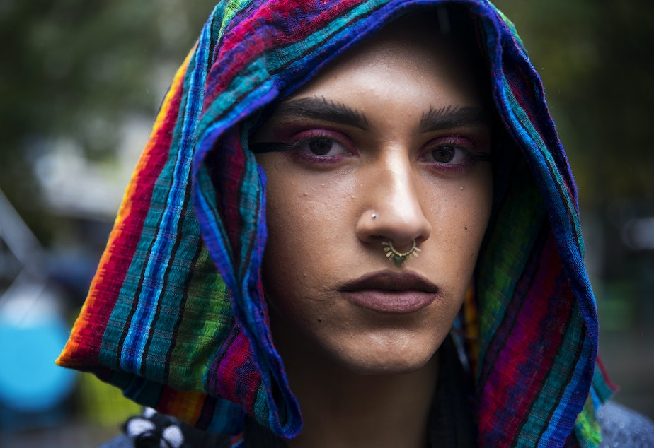 caption: Kenta Puv, 19, poses for a portrait during the Indigenous People's Day march and celebration on Monday, October 8, 2018, at Westlake Park in Seattle.