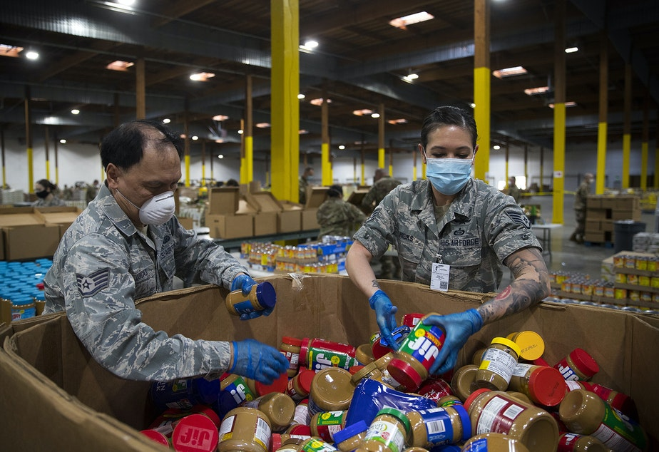 caption: Washington National Guard Airmen grab jars of peanut butter to add them to boxes along the assembly line at the Food Lifeline Covid Response Center on Tuesday, April 21, 2020,  along East Marginal Way South in Seattle.