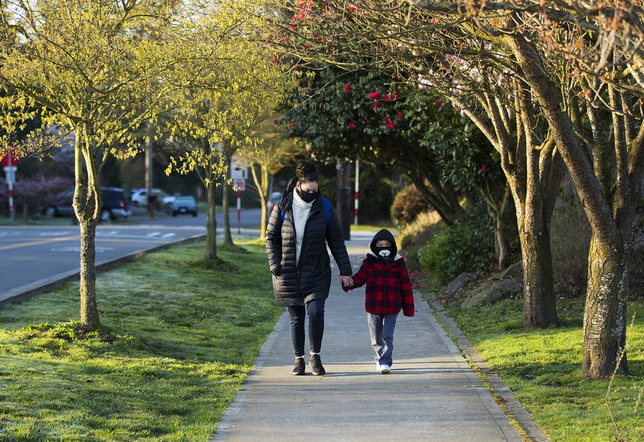 caption: Sandra Elizondo, left, and Edward Preciado, a 6-year-old kindergarten student at Northgate Elementary School, walk toward the building on Monday, April 5, 2021, on the first day of in-person learning at the school in Seattle.