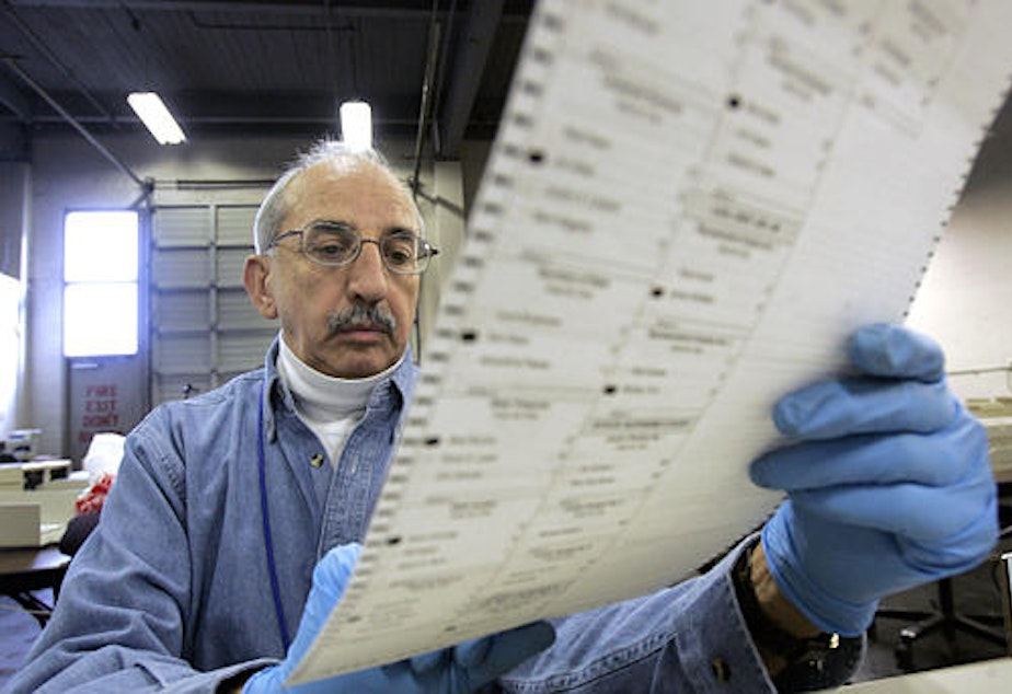 caption: FILE: Election worker Ed Faccone looks over a ballot to see why it would not read in a tabulating machine at a King County election tabulating center Wednesday morning, Nov. 17, 2004, in Seattle.