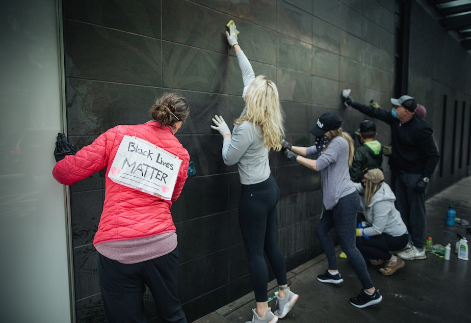 caption: Some of the people who went downtown on Sunday after the protests from the night before made it clear that they were not cleaning up as a criticism of those who protested against police violence the night before, but in support of their cause.