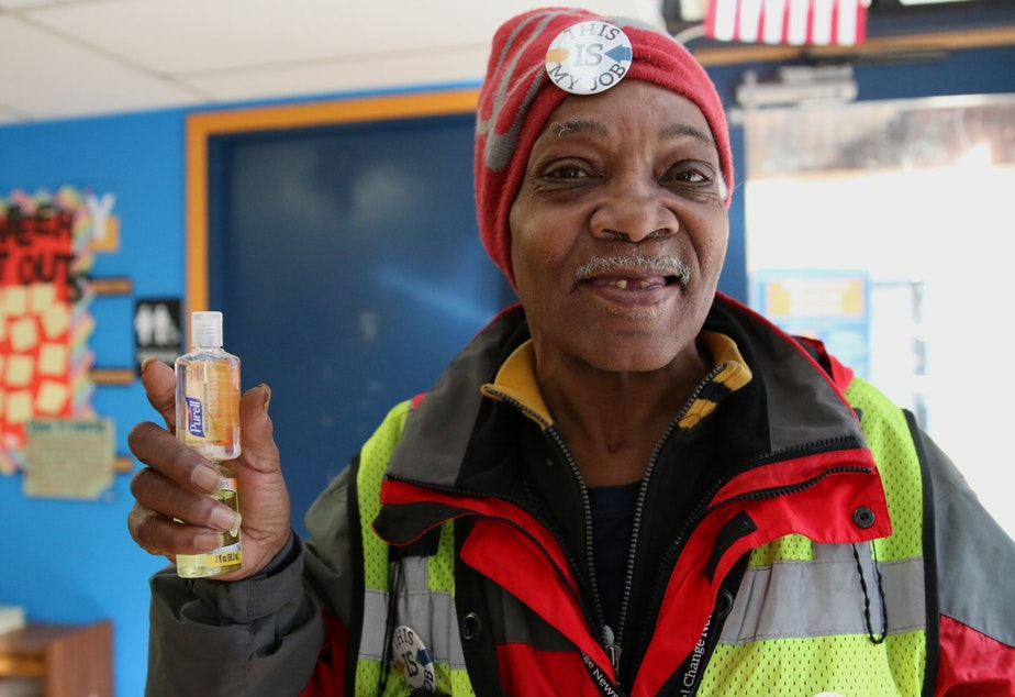 caption: David Canada Jones shows one of the Purell bottles he hands out to Real Change customers. Offering Purell has helped keep his sales up.