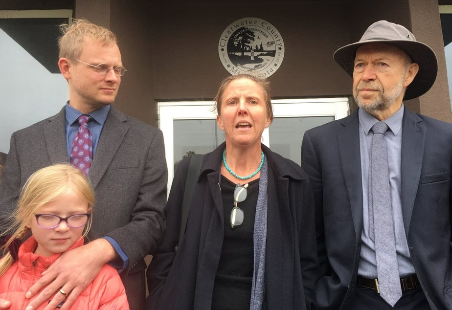 caption:  Defendant Emily Johnston (center) speaks outside Clearwater County courthouse, with co-defendant Ben Joldersma, left, and his daughter, and former NASA scientist James Hansen after she was acquitted along with two other defendants. Dan Kraker | MPR News