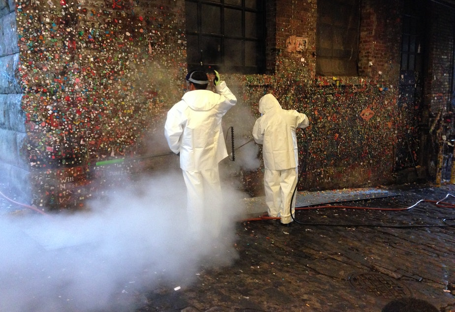 caption: Workers using steam cleaners to blast the gum off the walls of Post Alley below Pike Place Market on Tuesday, Nov. 10, 2015.