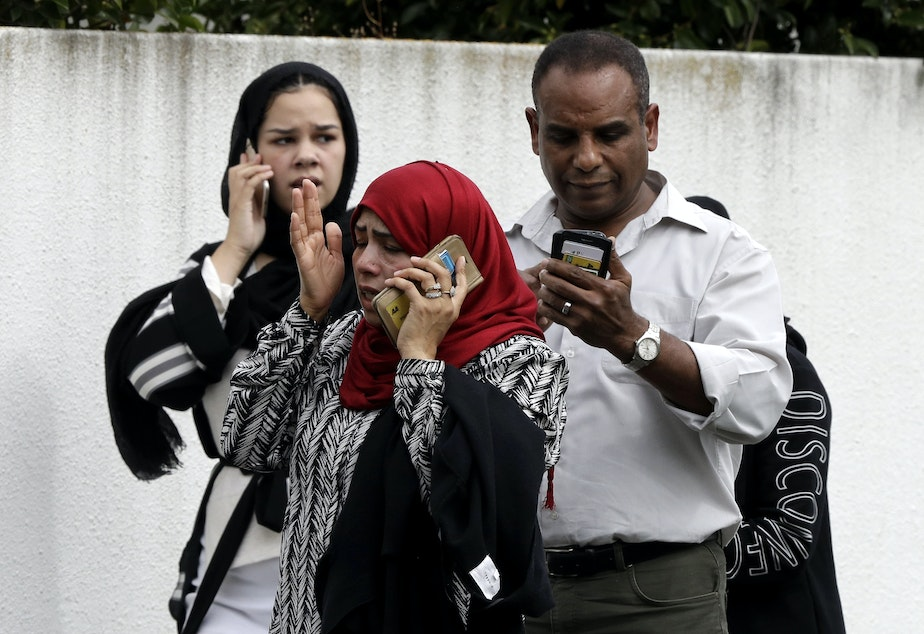 People wait outside a mosque in central Christchurch, New Zealand, on Friday after mass shootings in two locations.