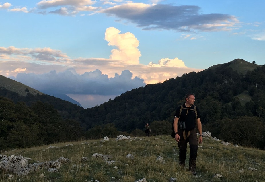 caption: Host Chris Morgan reaching a ridge high in the brown bear country of central Italy with amazing views of Europe's oldest beech forests