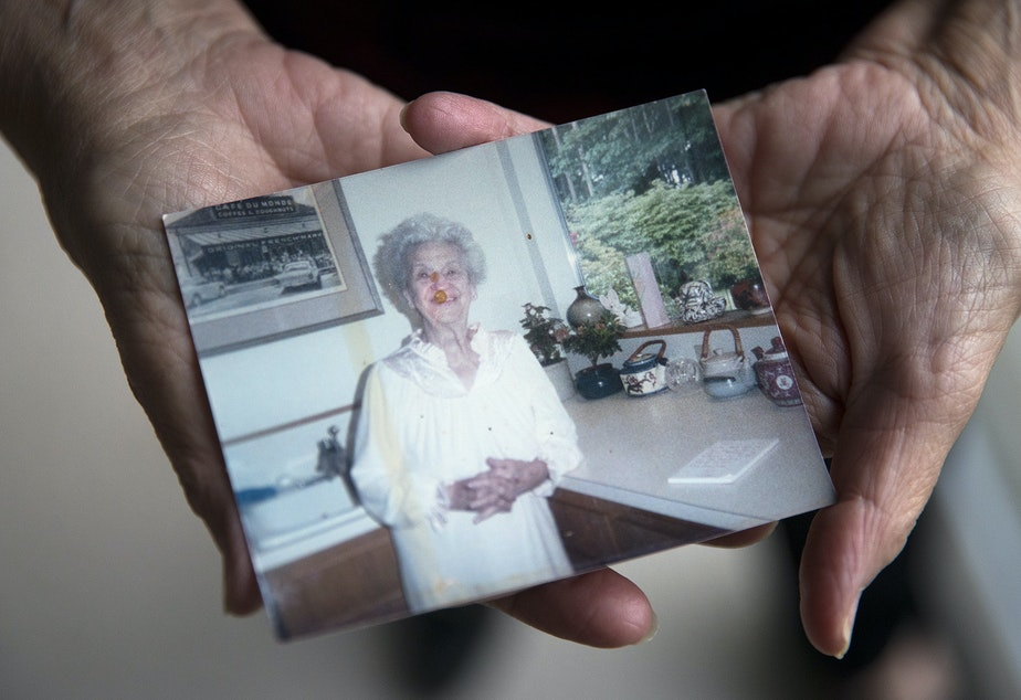 caption: Sheila Kelly holds a photograph of her mother, Helen May Kelly, on Friday, November 22, 2019, at her home in Seattle. The photo shows Helen on the Thanksgiving when she brought the mince pie to Sheila's house.