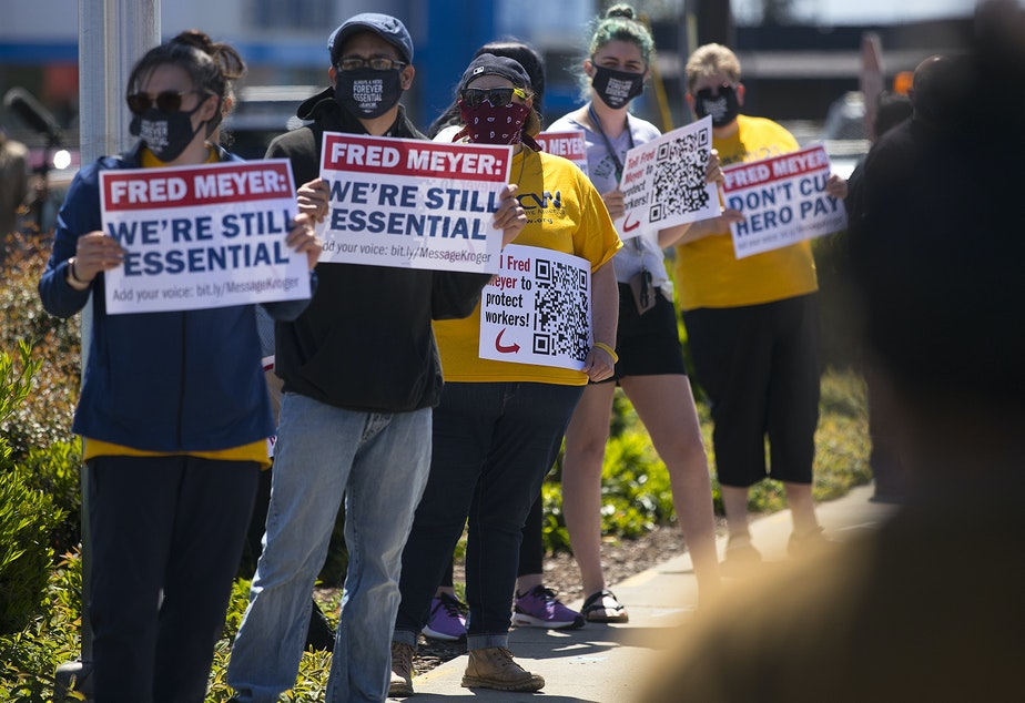 caption: The Don't Cut Hero Pay rally takes place on Friday, May 15, 2020, outside of Fred Meyer along 1st Avenue South in Seattle.